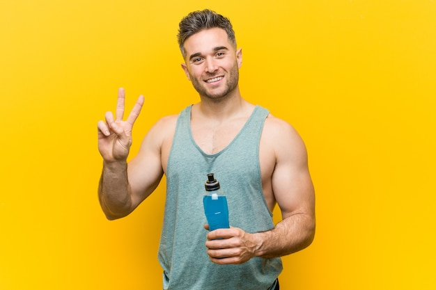 Blanke man met een energiedrank met overwinningsteken en breed glimlachend.