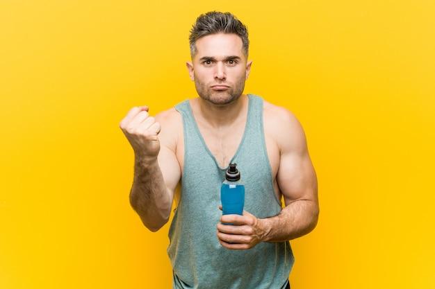 Blanke man met een energiedrank met vuist, agressieve gelaatsuitdrukking.