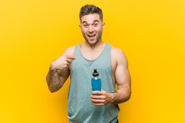 Blanke man met een energiedrank verbaasd wijzend op zichzelf, breed glimlachend.