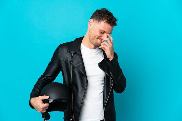 Blanke man met een motorhelm geïsoleerd op blauwe muur lachen