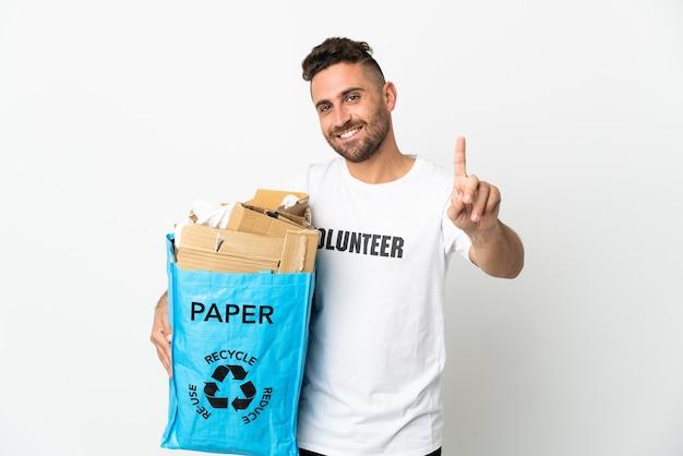 Blanke man met een recyclingzak vol papier om te recyclen geïsoleerd op een witte achtergrond die een vinger laat zien en optilt