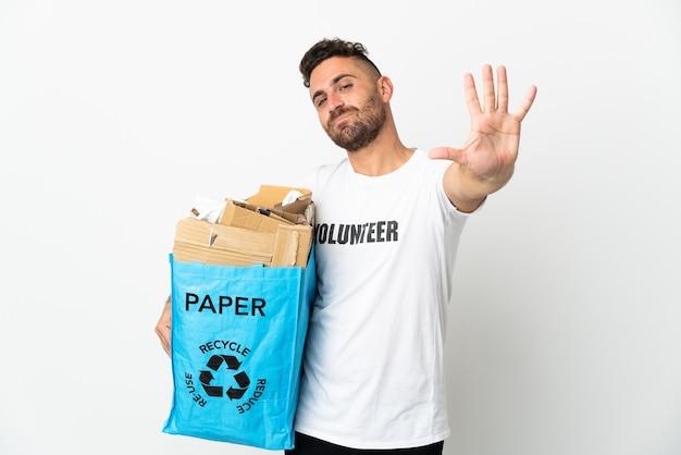 Blanke man met een recyclingzak vol papier om te recyclen geïsoleerd op een witte achtergrond die vijf met vingers telt