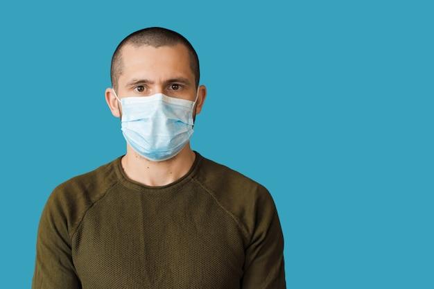 Blanke man met een wit medisch masker op gezicht kijkt naar de voorkant op een blauwe muur met vrije ruimte