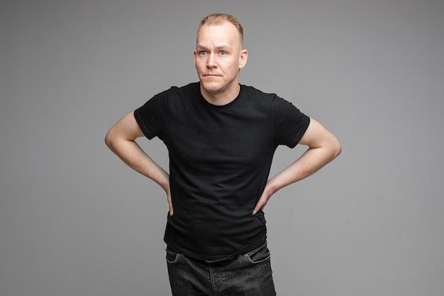 Blanke man met een zwart t-shirt en spijkerbroek poseren voor de camera met de handen aan een riem op een grijze achtergrond