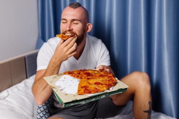 Blanke man met fast food thuis in de slaapkamer op bed