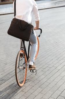 Blanke man met formele kleding, rijden op de fiets op straat in de stad