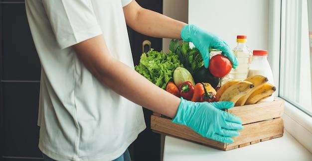 Blanke man met groene medische handschoenen na het kopen van producten voor thuis tijdens de quarantaine