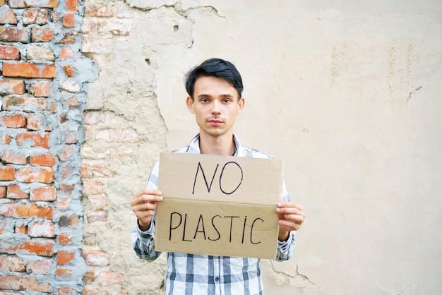 Blanke man met het opschrift geen plastic milieubeschermingsconcept tegen afvalvervuil...
