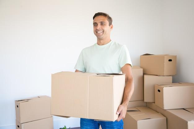 Blanke man met kartonnen doos in zijn nieuwe huis of appartement