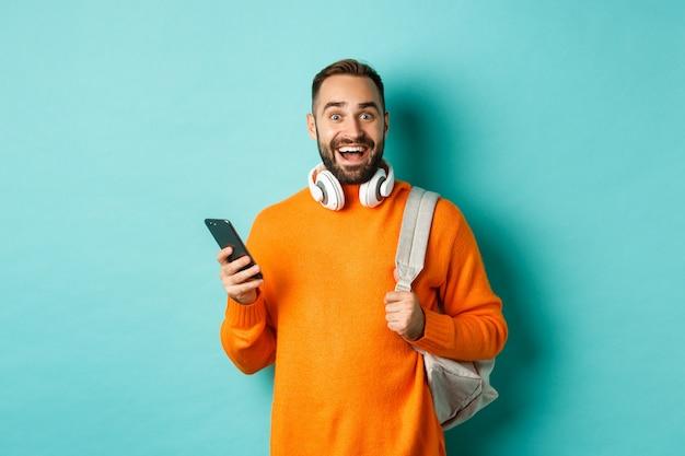Blanke man met koptelefoon en rugzak verbaasd na het lezen van telefoonnotificatie