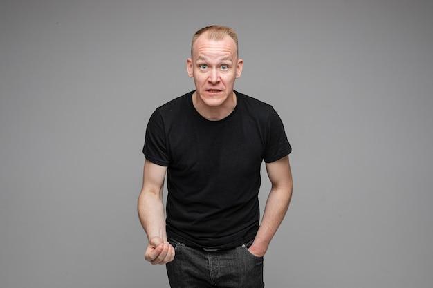 Blanke man met kort blond haar met een zwart t-shirt en spijkerbroek is boos en probeert iets uit te leggen