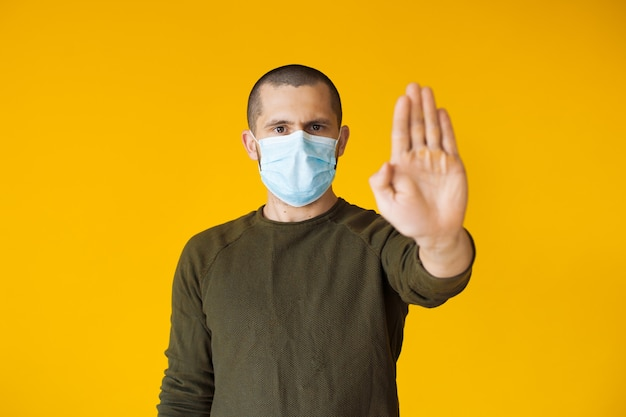 Blanke man met kort haar poseren op een gele muur gebaart stop terwijl hij een speciaal wit masker draagt