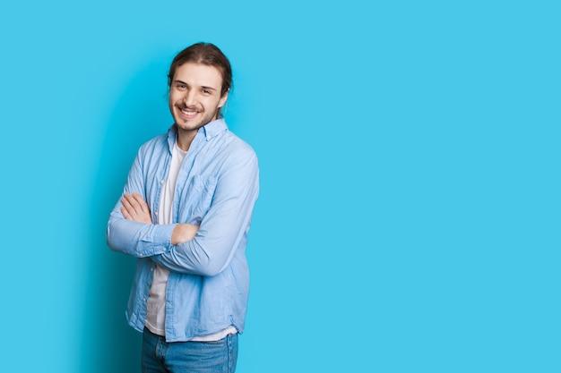 Blanke man met lang haar en baard poseren tijdens het kruisen van handen op een blauwe muur met vrije ruimte