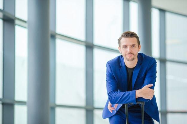 Blanke man met mobiel op de luchthaven tijdens het wachten op instappen