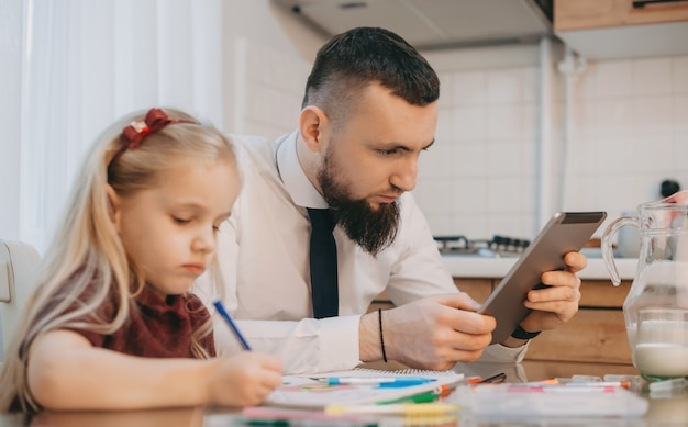 Blanke man met mooie baard kijkt naar zijn gadget terwijl een blond meisje naast hem iets schrijft