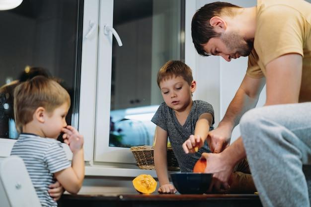 Blanke man met zijn zonen die ogen uitsnijden op een pompoen om traditionele jack-lantaarn te maken. . hoge kwaliteit foto