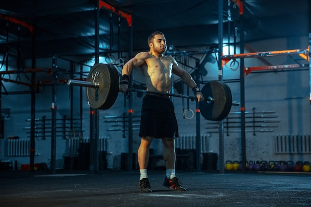 Blanke man oefent in gewichtheffen in de sportschool close up van mannelijk sportief model