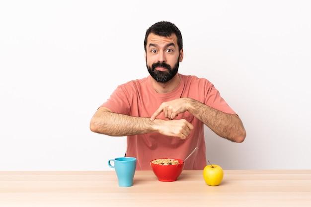 Blanke man ontbijten in een tafel die het gebaar maakt om te laat te zijn.