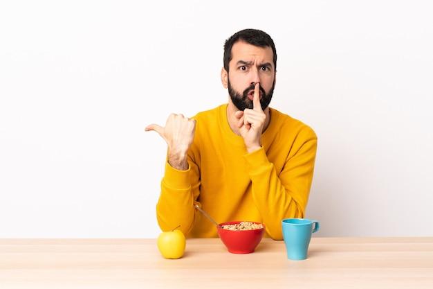 Blanke man ontbijten in een tafel die naar de zijkant wijst en stilte gebaar doet.