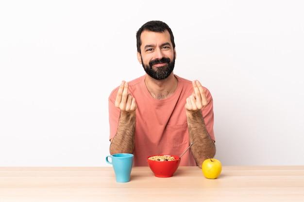 Blanke man ontbijten in een tafel geld gebaar maken.