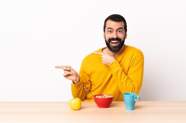 Blanke man ontbijten in een tafel verrast en wijzende kant.