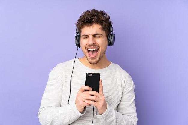 Blanke man op paarse muur luisteren muziek met een mobiel en zingen