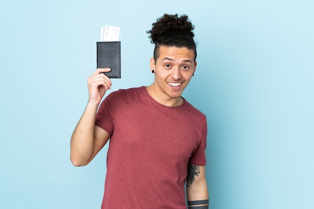 Blanke man over geïsoleerde blauwe muur gelukkig in vakantie met paspoort en vliegtickets