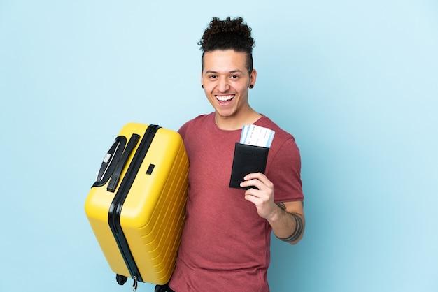 Blanke man over geïsoleerde blauwe muur in vakantie met koffer en paspoort
