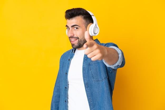 Blanke man over geïsoleerde gele muur muziek luisteren en naar voren wijzend