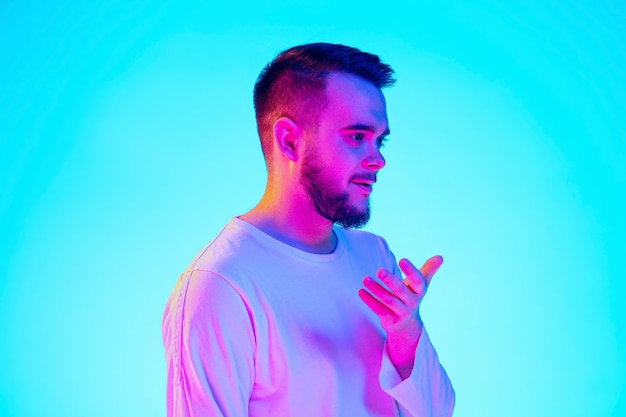 Blanke man portret geïsoleerd op blauwe studio achtergrond in neonlicht. prachtig mannelijk model. concept van menselijke emoties, gezichtsuitdrukking, verkoop, advertentie. copyspace voor advertentie.