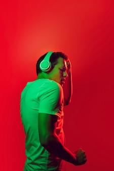 Blanke man portret geïsoleerd op een rode achtergrond in veelkleurige neonlicht.