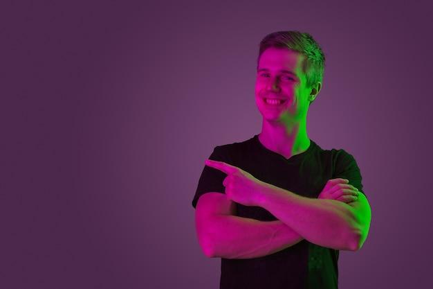 Blanke man portret geïsoleerd op paarse studio in neonlicht
