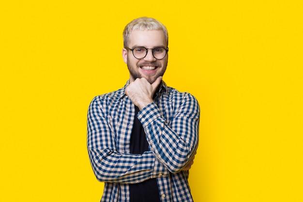 Blanke man raakt zijn bebaarde kin aan en lacht naar de camera op een gele muur met een bril en een shirt aan