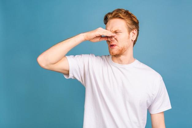 Blanke man ruikt iets stinkends en walgelijks, adem inhoudend met vingers op neus
