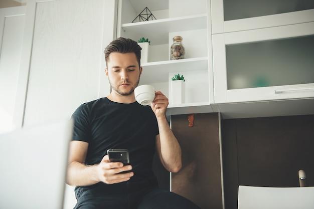 Blanke man rusten en drinken van een kopje koffie tijdens het chatten op de telefoon en op afstand thuis werken
