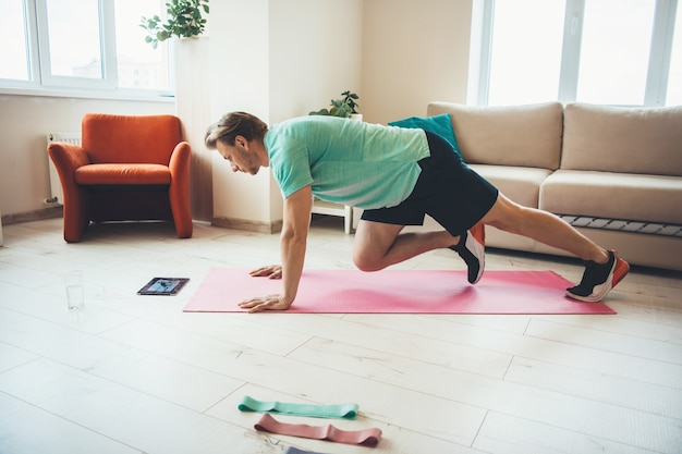 Blanke man sport oefeningen thuis terwijl kijken naar de tablet op de vloer