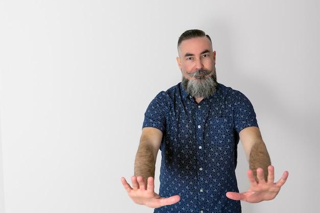 Blanke man van jaar oud met een grote halfgrijze baard met een ernstig gezicht en handen naar voren in een duidelijk teken dat hij hem beveelt te stoppen