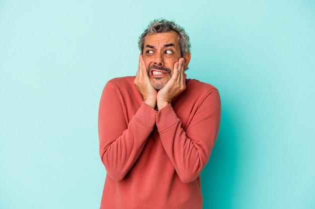 Blanke man van middelbare leeftijd geïsoleerd op blauwe achtergrond bang en bang.