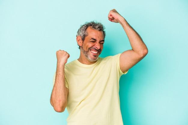 Blanke man van middelbare leeftijd geïsoleerd op blauwe achtergrond die een speciale dag viert, springt en armen met energie opheft.