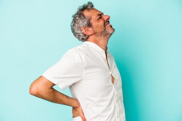 Blanke man van middelbare leeftijd geïsoleerd op blauwe achtergrond die lijdt aan rugpijn.