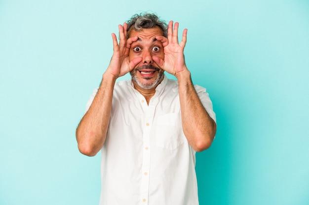 Blanke man van middelbare leeftijd geïsoleerd op blauwe achtergrond die ogen open houdt om een succeskans te vinden.