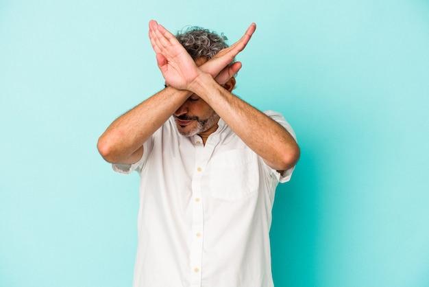 Blanke man van middelbare leeftijd geïsoleerd op blauwe achtergrond die twee armen gekruist houdt, ontkenningsconcept.
