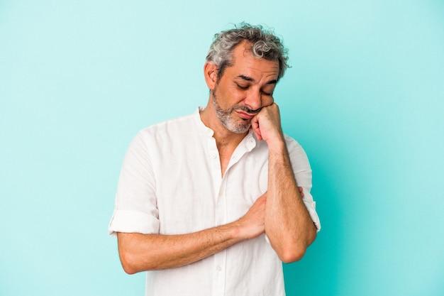 Blanke man van middelbare leeftijd geïsoleerd op blauwe achtergrond die zich verdrietig en peinzend voelt, kijkend naar kopieerruimte.