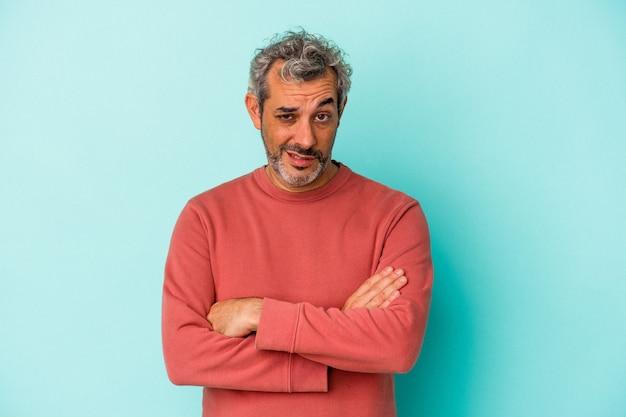 Blanke man van middelbare leeftijd geïsoleerd op blauwe achtergrond die zich verveelt, vermoeid is en een ontspannen dag nodig heeft.