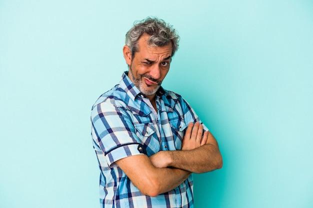 Blanke man van middelbare leeftijd geïsoleerd op blauwe achtergrond fronsend gezicht in ongenoegen, houdt armen gevouwen.