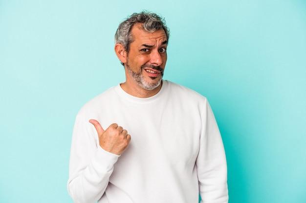 Blanke man van middelbare leeftijd geïsoleerd op blauwe achtergrond geschokt wijzend met wijsvingers naar een kopieerruimte.