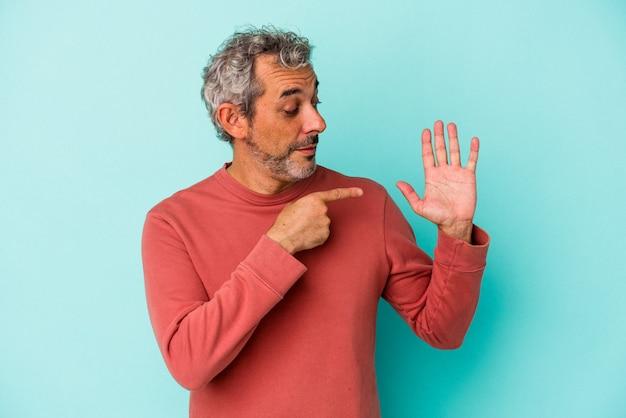 Blanke man van middelbare leeftijd geïsoleerd op blauwe achtergrond glimlachend vrolijk met nummer vijf met vingers.
