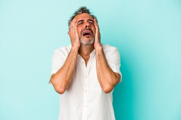 Blanke man van middelbare leeftijd geïsoleerd op blauwe achtergrond huilen, ongelukkig met iets, pijn en verwarring concept.
