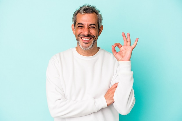 Blanke man van middelbare leeftijd geïsoleerd op blauwe achtergrond knipoogt en houdt een goed gebaar met de hand.