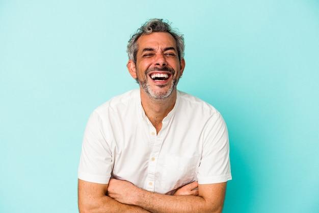 Blanke man van middelbare leeftijd geïsoleerd op blauwe achtergrond lachen en plezier maken.